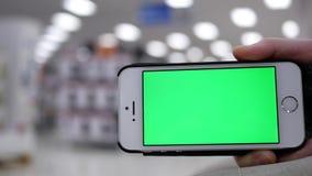 Женщина держа зеленый мобильный телефон экрана на красивой запачканной освещая предпосылке внутри магазина Walmart