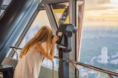 Женщина смотрит городской пейзаж Куалаа-Лумпур Панорамный вид вечера горизонта города Куалаа-Лумпур на небоскребах захода солнца стоковые фотографии rf