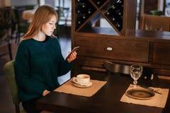 Женщина с взглядами чашки кофе в смартфоне в кафе стоковые фотографии rf