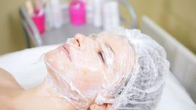 Женщина с маской на ее стороне делая косметический очищать процедур mesotherapy стороны в клинике косметологии акции видеоматериалы