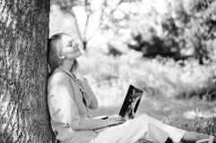 Женщина с ноутбука работы деревом outdoors постным Минута для ослабляет Технология образования и концепция интернета Работа девуш стоковое фото