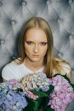 Женщина с цветками гортензии на серой стене стоковая фотография rf