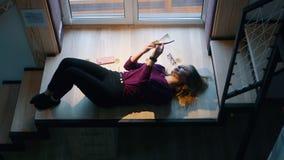 Женщина читает книгу лежа на лестницах окном Избежание реальности акции видеоматериалы