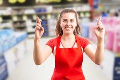 Женщина работая на супермаркете держа пальцы пересеченный стоковое фото rf