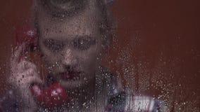 Женщина ретро стиля белокурая за влажным окном говорит по старому красному телефону сток-видео