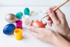 Женщина рисуя пасхальные яйца стоковое фото rf