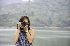 Женщина руки держа камеру принимая запруду Nakhon Nayok Bon Wang предпосылки изображений, Таиланд стоковое фото