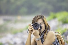Женщина руки держа камеру принимая запруду Nakhon Nayok Bon Wang предпосылки изображений, Таиланд стоковые фото