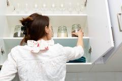 Женщины комплектуя деталь от hutch хранения Умная концепция организации кухни стоковое фото
