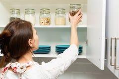 Женщины комплектуя деталь от hutch хранения Умная концепция организации кухни стоковые изображения