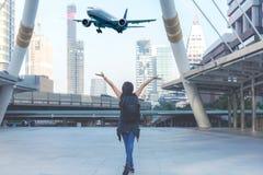 Женщины путешественника планируют и укладывают рюкзак видят самолет в аэропорте в современном городе Азиатская свобода и ослабить стоковые изображения