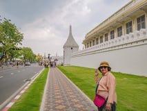 Женщины портрета старшие азиатские со стеной виска Wat Phrakeaw в главном виске Бангкока стоковые изображения rf