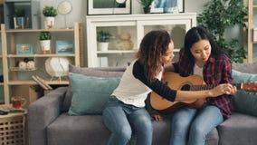 Жизнерадостная Афро-американская девушка учит, что ее азиатский друг играет гитару дома Молодые женщины сидят на софе сток-видео