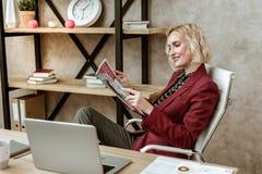 Жизнерадостная внимательная женщина отдыхая на белом кресле офиса стоковая фотография rf