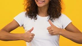Жизнерадостная девушка показывая большие пальцы руки вверх, радующся успех, поддерживая правый выбор сток-видео