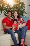 Жизнерадостная стильная мать, отец и их прелестный ребенк отдыхая на софе стоковое изображение