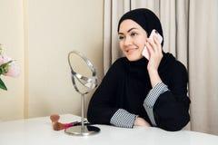 Жизнерадостная счастливая милая мусульманская женщина сидя и используя мобильный сотовый телефон вызывая для друга беседуя во вре стоковые изображения