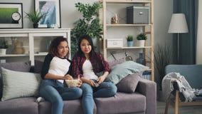 Жизнерадостные друзья смотрят ТВ дома, едят попкорн и говорят обсуждающ фильмы и рекламы Девушки усмехаются видеоматериал