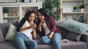 Жизнерадостные студенты азиат и афроамериканец говорящ и смеющся смотрящ экран смартфона используя сидеть устройств сток-видео