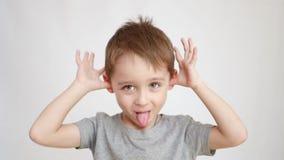 Жизнерадостный, счастливый смех ребенка пока смотрящ в камеру Мальчик показывает обезьяну Эмоции малого ребенка видеоматериал