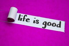 Жизнь хороший текст, концепция воодушевленности, мотивации и дела на пурпурной сорванной бумаге стоковое изображение