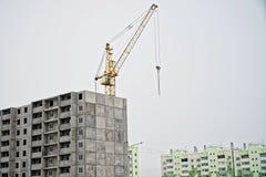 жилой дом Мульти-этажа и кран в стадии завершения конструкции на фоне построенных домов стоковые изображения