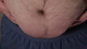 Жирный человек касаясь его жирному животу акции видеоматериалы