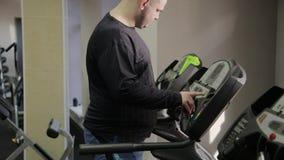 Жирный человек получает на третбане в спортзале акции видеоматериалы