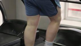 Жирный человек работая на третбане в спортзале сток-видео