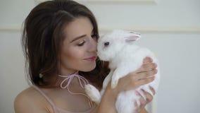 Заботя беременная женщина 40 лет игр с маленьким белым зайцем в ее доме конец вверх видеоматериал