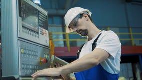 Заводской рабочий управляет контрольной панелью сток-видео