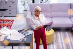 Завораживающий пожилой ведущий женский дизайнер проверяя качество материалов одежды стоковое фото