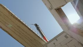 Заграждение крана держит огромную надземную панель над стенами дома Нижний взгляд видеоматериал