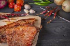 Зажаренная свинина на разделочной доске, помещенной на деревянном столе со специями помещенными вокруг стоковое изображение