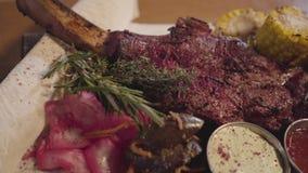 Зажаренное мясо с косточкой нервюры лежа на пите с красной капустой, мозоль, грибы, морковь и соусы закрывают вверх Служа еда вну видеоматериал