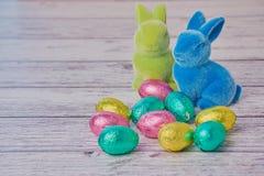 Зайчики пасхи за покрашенными яйцами шоколада стоковые фотографии rf