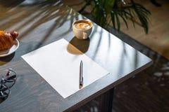 Закройте вверх кофейной чашки, круассана, стекел, чистого листа и ручки на таблице стоковые фото