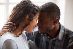 Закройте вверх любить черное объятие пар смотря в глазах стоковая фотография rf