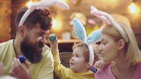 Закройте вверх матери, отца и их сына крася пасхальные яйца Счастливая семья подготавливая для пасхи семья ее целуя сынок портрет видеоматериал