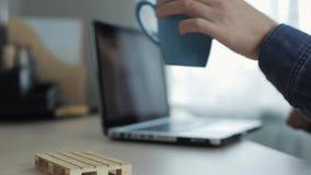 Закройте вверх чашки чаю или cofee против мужских рук печатая на ноутбуке на предпосылке Домашний фрилансер работая на столе сток-видео