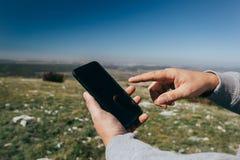 Закройте вверх человека используя телефон на открытом воздухе стоковая фотография