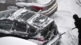 Замедленное движение снега людей очищая и лед с ее окна ветровой защиты автомобиля