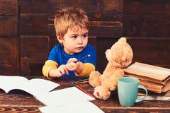 Занятый ребенк в школе Небольшой мальчик сидя на деревянном столе с тетрадями с прописями Белокурый ребенок смотря его плюшевый м стоковые фото
