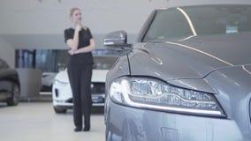 Запачканная диаграмма женщины в черном положении носки в мотор-шоу смотря вокруг Фара современного серебряного автомобиля в видеоматериал