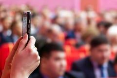 запачканный Блоггер или журналист прямого вещания используя мобильный телефон в аудитории Розовая предпосылка Вертикальные фото и стоковая фотография
