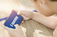 Задний задний взгляд-азиатский мальчик с милым, со смотреть планшет в руке, онлайн уча концепциях и обучении по Интернету с учить стоковые изображения