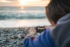 Задний конец взгляда вверх по молодому человеку снимая видео или фотографируя фото на его мобильном сотовом телефоне во время его стоковая фотография rf