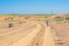 Задний фотограф hiker взгляда идет на дорогу в полу-пустыне стоковое изображение