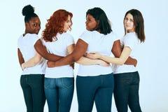 Задняя сторона смешанной группы лицо одной расы женщин в случайный выглядеть счастливый совместно на белизне стоковые фото