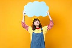 Задумчивый милый подросток девушки во французском берете, sundress джинсовой ткани смотря вверх на голубом пустом пробеле говорят стоковая фотография rf